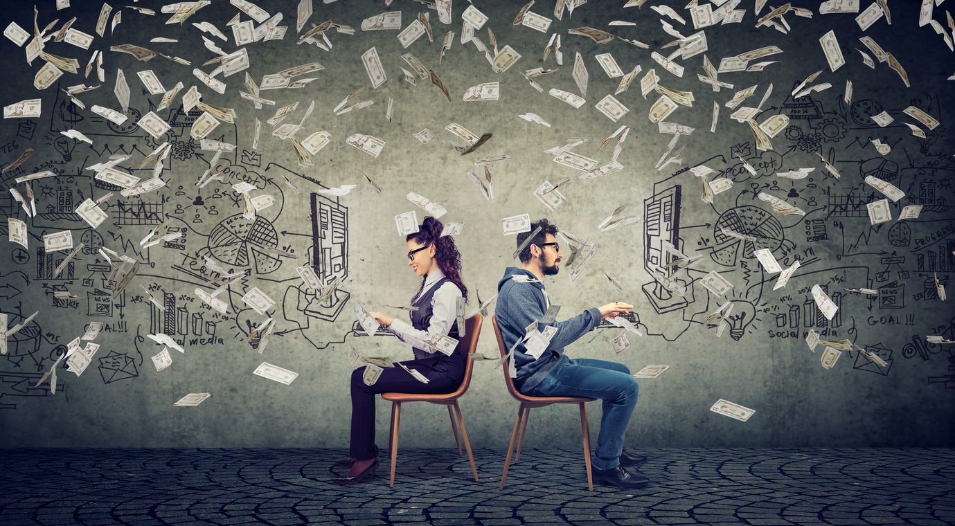 Business man and businesswoman working on computer developing successful strategy under money rain