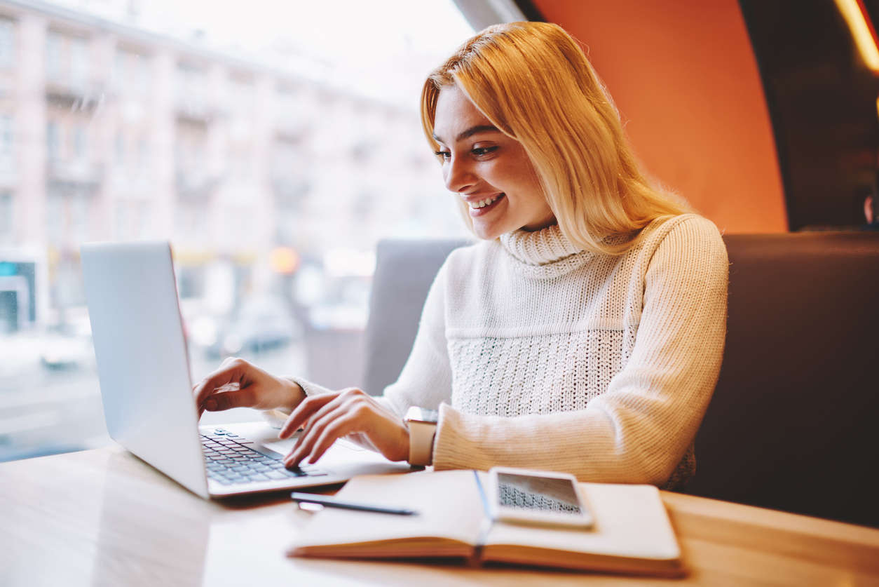 Cheerful young woman excited with sales on web store page making shopping on laptop computer, overjoyed female freelancer amazed with prosperous income from online business reading mails on netbook