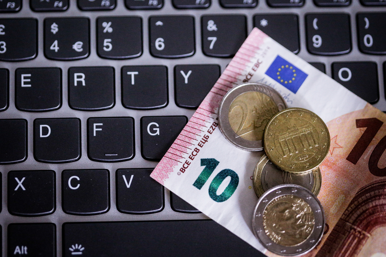 Euro coins and notes on laptop's keyboard